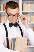 foto of bow tie hair  - Confident young man in shirt and bow tie holding book and adjusting glasses while standing in library - JPG