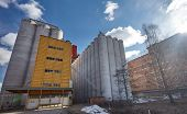 stock photo of silos  - Factory exterior with big concrete grain silos and manufacturing building in Finland on a sunny spring day - JPG