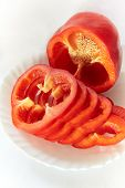 image of pepper  - Red bell pepper lies on a white plate on a white background elegant shiny surface pepper seen grain core pepper cut into pieces beautiful curly rings juicy shadow on a plate a shadow on the background appetizing - JPG