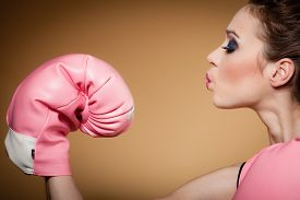 picture of boxers  - Sporty woman female boxer model wearing big fun pink gloves playing sports boxing studio shot brown background - JPG