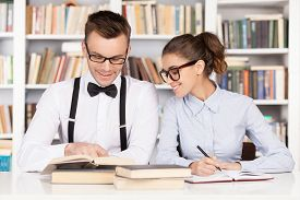 stock photo of nerd glasses  - Cheerful young nerd couple in glasses preparing to exams while sitting together at the library - JPG