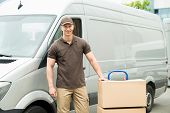 stock photo of moving van  - Young Happy Delivery Man With Cardboard Boxes On Trolley In Front Of Van - JPG