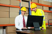 picture of warehouse  - Portrait Of Happy Warehouse Worker And Manager Using Computer In A Warehouse - JPG