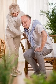 stock photo of love hurts  - Senior man with back pain and his helpful loving wife - JPG