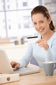 Young woman using laptop, shopping on internet, using credit card, smiling.?