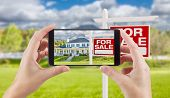Female Hands Holding Smart Phone Displaying Photo of For Sale Real Estate Sign and House Behind. poster
