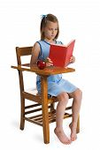 picture of illiteracy  - Young girl reading a red book at a wooden school desk - JPG