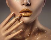Fashion art Golden skin Woman face portrait closeup. Beauty gold nail ring, Lips and Skin. Model gir poster
