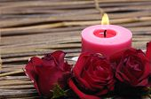 Vela roja y una rosa roja en la estera de bambú