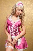 sexy blonde woman in pink seductive dress on golden background