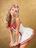 sexy blonde woman in seductive nurse costume on golden background
