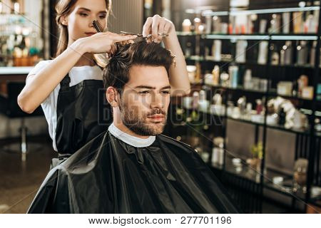 poster of Beautiful Young Hairdresser Cutting Hair To Handsome Man In Beauty Salon