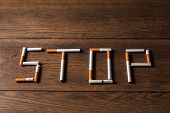 Creative Background, The Word Stop Is Made Up Of Cigarettes On A Brown Wooden Background. The Concep poster