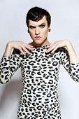 Transvestit mit Tätowierung In Leopard Kleid, Frisur und Gesicht In die Kamera schauen