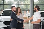 Couple Making Deal With Manager Of Car Dealership, Buying Automobile. Bearded Man Shaking Hands With poster