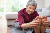 Closeup of senior woman stretching to touch toes while sitting on yoga mat. Portrait of mature woman poster