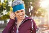 Portrait of smiling senior woman listening to music after running. Healthy mature woman wearing blue poster