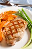 stock photo of pork chop  - Grilled pork chop with orange glazed carrot and spring onion - JPG