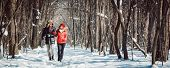 Couple having a winter walk on a chilly cold day in the woods down a path in the snow poster