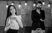 Man With Beard And Young Lady Teacher Stand In Classroom, Chalkboard On Background. Generation Conce poster
