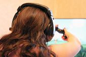 Girl With Headphones Playing Video Game With Joystick At Home, Back View. Gamepad In Female Hands, G poster