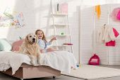Adorable Kid And Golden Retriever Sitting On Bed Together In Children Room, Child Pointing On Someth poster