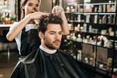 Beautiful Young Hairdresser Cutting Hair To Handsome Man In Beauty Salon poster