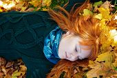 Beautiful Woman Lying On Fall Leaves
