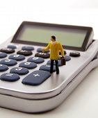 Miniature Accountant Standing On Calculator