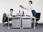 Side view of a businesswoman passing folders to male colleague across the desk