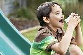 Side view of young boy on slide using inhaler in park