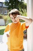 Portrait of young boy with tissue paper rubbing eye in backyard