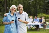 Portrait of happy senior couple holding wine glasses with family having lunch in background