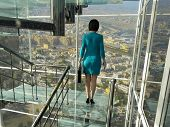 Business woman rises on the glass stairs against the background of the city.