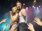 Young man and woman singing on stage in concert in front of adoring fans