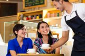 Asian female friends enjoying her leisure time in a cafe, drinking cappuccino and talking about some things, a Indonesian waiter serving the coffee