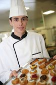 Young pastry cook holding tray of pastries