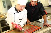 Student in pastry making cookies with help of teacher
