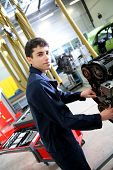 Student in mechanics working on car engine