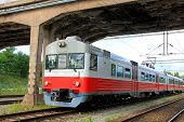 stock photo of commutator  - Red commuter train under bridge at railway station - JPG
