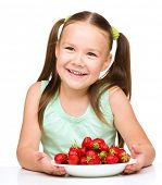 Cheerful little girl is eating strawberries, isolated over white