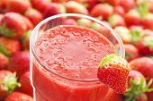 Strawberry smoothie with strawberry fruits in the background