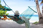 Woman In Hat Lying In Hammock In Tree's Shadow On A Beach