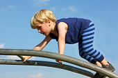 foto of playground  - A cute little boy is carefully climbing a ladder toy at the playground on a summer day - JPG