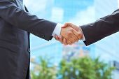 Business associates shaking hands beginning their partnership