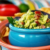 A bowl of fresh guacamole with corn tortilla chips. Intentional shallow depth of field.