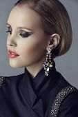stock photo of blazer  - Portrait of beautiful blond woman with studio pulled back wearing diamante statement earrings and blazer with beads on studio background - JPG