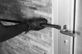 picture of unsafe  - Thief with a bar of iron in the hand to open a door - JPG