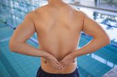 Fit swimmer touching his back by the pool at the leisure center