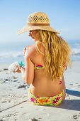 Gorgeous woman sitting on the beach in sunhat applying suncream on a sunny day